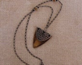 Wooden triangle necklace with top overlay silver and black flower motif.