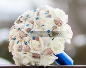 Royal blue seashell bouquet with cream roses for beach and destination wedding with horizon blue sapphire blue handle and crystal pins