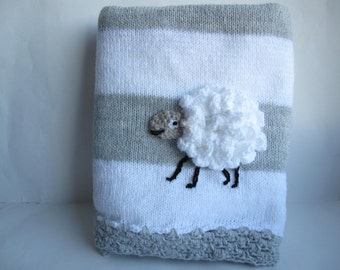 Grey and white knitted baby blanket with a crochet sheep