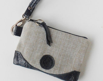 Soft gray wristlet with embossed leather trim.