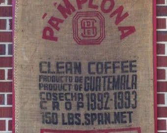 Burlap coffee bean bag on a red wooden frame