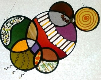 This Gorgeous Stained Glass Panel is a high quality and unique piece.  Made with a variety of techniques, with a fun and funky design.
