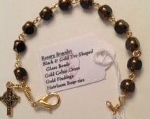 Rosary Bracelet handcrafted of Black Tri-shaped Glass Beads edged in Gold paint, with Gold links, chain, and wire, and a gold Celtic Cross