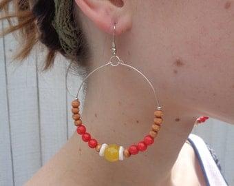 Handmade boho beaded hoop earrings in red, orange, and yellow for spring.