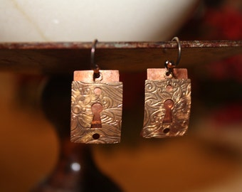 Locked up!  Hammered copper earrings with bronze escutcheon.
