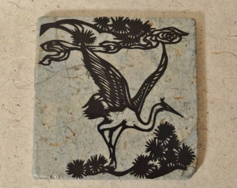 Trivet: Paper-covered stone with hand-cut crane design
