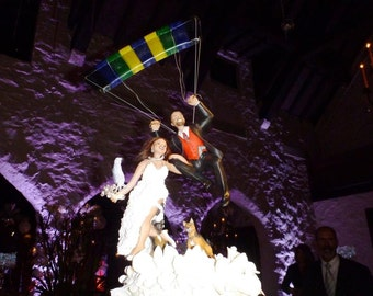 Customized wedding topper with your looks, includes a couple of dogs, parrot and a parachute.