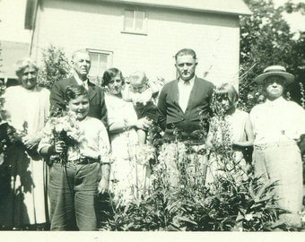 Chubby Boy Holding Bouquet of Flowers 1920s Family Group Picture in Garden Vintage Black and White Photo Photograph
