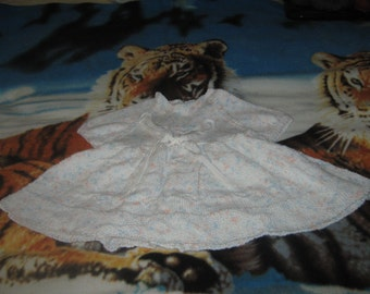 a white babys dress with flecks of colour size 18-20in
