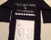 DISCOUNTED -- Nearly Perfect -- #63b, see photos -- I just got here & I'm already awesome.  -- black snapsuit, size 0-3 months