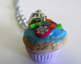 Cute polymer clay blue raspberry with fruit toppings and sprinkles cupcake necklace with silver toned chain
