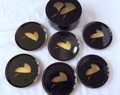 Six black and gold coasters in their original box, with stork or crane decoration, by Melarti