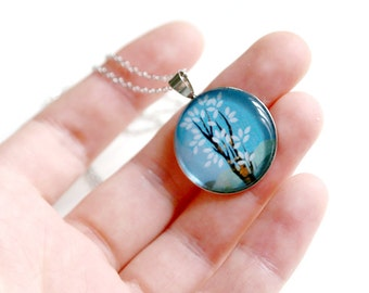 Silver pendant necklace with linocut illustration of a blue tree