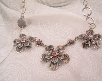 Silver  tone chain necklace, with three ornate flowers. With pink crystal color center, with a magnetic clasp