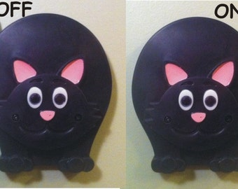 Black cat light switch cover with switching tail