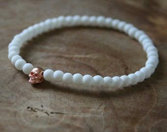 White Rosé Skull: an elastic beaded bracelet with rosegold skull and matte white glass beads.