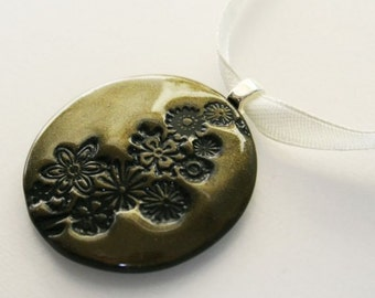 Gold and Olive - an one of a kind polymer clay pendant in olive green with a metallic golden shine and an imprint of a row of flowers