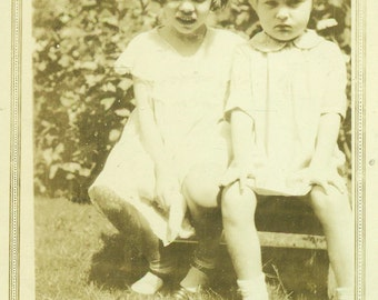I am NOT Happy Frowning Little Girl Sitting With Sister on Outside Bench 1930s Vintage Black and White Photo Photograph