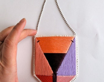 Embroidered pendant necklace with colorblock geometric design in peaches, purples and red with silver ball chain