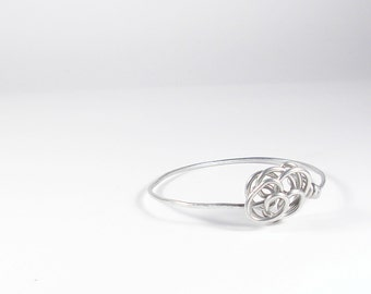 Aluminium wire bracelet with stylized flower. Silver color bangle.