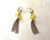 Exotic earring with pompom of chains and yellow and green beads.