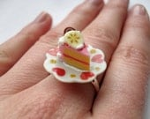 Mini pink and white frosted cake on a plate ring