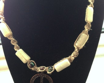 Onyx and Peace hemp necklace made by Christine H. Rietsch with wood clasp and brass pendant.