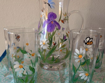 Set of eight tall drinking  glasses and tall fleur de lis pitcher with daisies .
