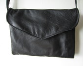 small black leather purse with flap and colorful interior