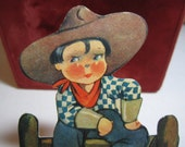 Adorable 1930's die cut Valentine card rosy cheeked young cowboy sitting on a fence with his lasso