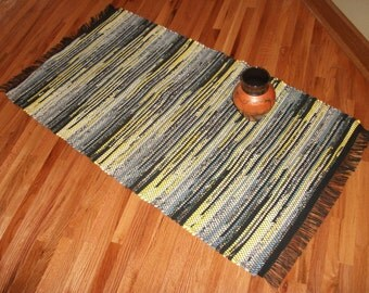 Hand-woven, rag rug, made of recycled fabric and sheets, in black, white,  gray, and shades of yellow