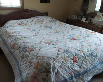 Pieced and appliqued bed quilt