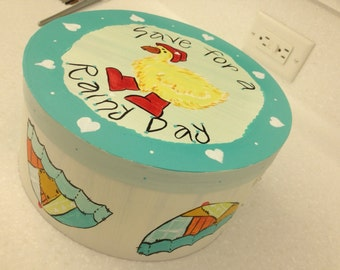 """9"""" diameter x 4"""" Tall, wood box with lid.  Duck in Galoshes Painted on Top with Acrylics. Umbrellas on the sides."""