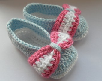 Crochet baby shoes for babies age 3-6 months. Pale blue, white sole, pink and white bow detail