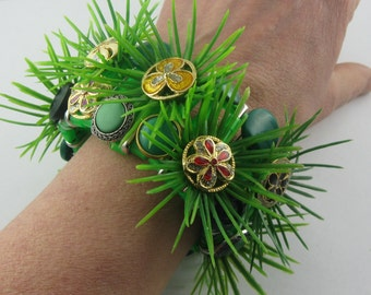 """Button bracelet """"FLOWER MEADOW"""" from flower buttons made of metal, grass pieces from plastic and more. Size M. Collection: """"button & buckle"""""""