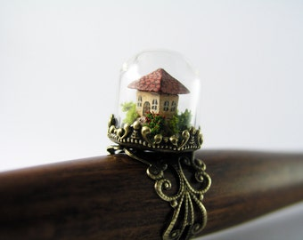 Miniature world. Tiny little house amidst garden in a glass dome ring.