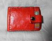 Red, leather, slim, bi-fold wallet with snap closure.