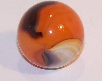 Glass Marble with orange base, black, green, and white streaks
