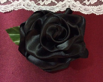 Handcrafted black satin ribbon rose hair accessory.