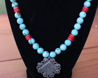 Turquoise genuine stone and red coral bead necklace with unique silver toned pendant with burnished finish.