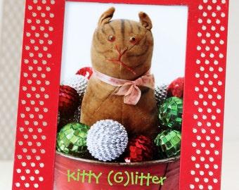 "Framed notecard of ""kitty (g)litter"" vintage toy cat"