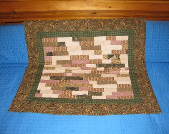 This quilted table runner or wall hanger is a scrappy mix of colors surrounded by a border of pine cones.