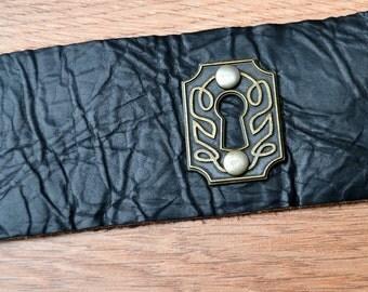Dark brown leather cuff bracelet with escutcheon / key hole