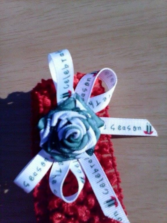 Green and white rose on 'Celebrate the season' bow adorning red crochet elastic headband