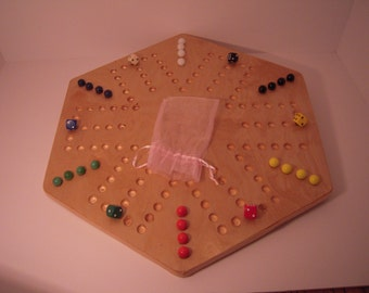 The infamous Aggravation Game Board includes 24 glass marbles and 6 color matched dice.