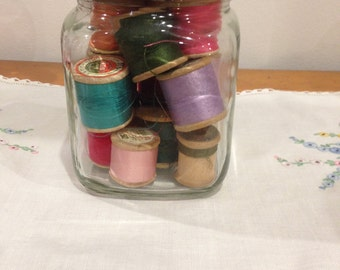 vintage glass jar filled with vintage wooden cotton reels