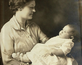 Antique mother and baby photo. Studio portrait. Mother daughter picture. Circa 1910s Mother's Day. Love. Sepia card. Black and white