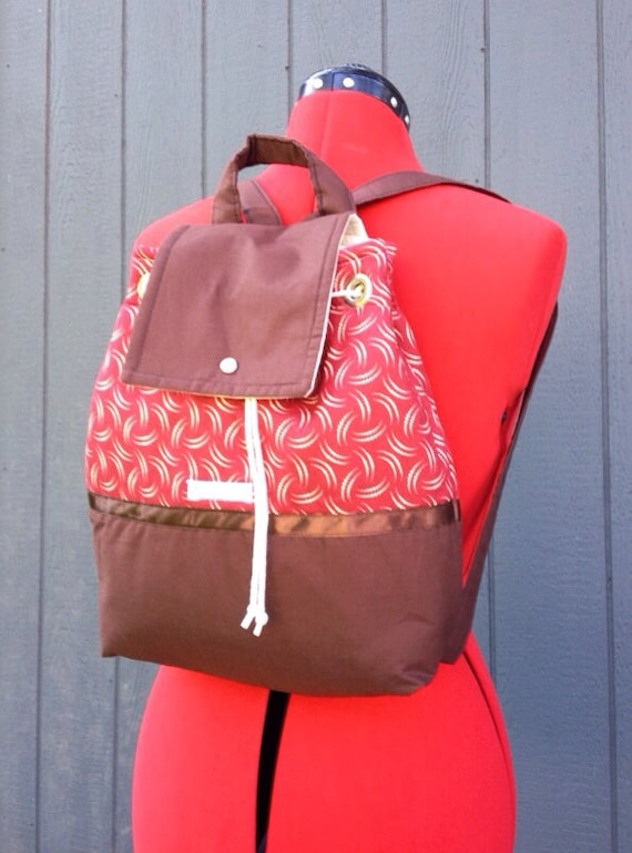 Red and brown backpack, diaperbag, overnight bag.  Drawstring, snap closure