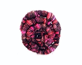 Sacred geometry spiral is the focal point of pink and black sister ring.
