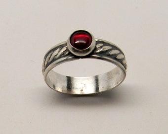 Sterling silver stacking ring with garnet gemstone.